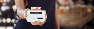 Close Up Of Waitress Holding Credit Card Payment Terminal In Busy Bar Restaurant